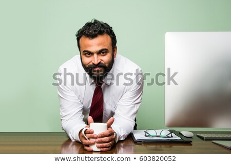 A young executive looking at camera confidently while isolated o Stock photo © HASLOO