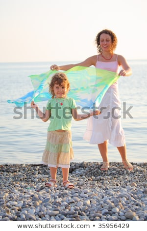 Mother with daughter stand on seacoast with shawl in hands Stock photo © Paha_L