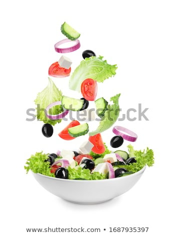 A bowl with an appetizing vegetable salad with cheese and a fork in the hands of a girl . Healthy Vi Stock photo © artjazz