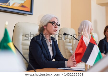 Serious mature female delegate in elegant suit listening to audience Stock photo © pressmaster
