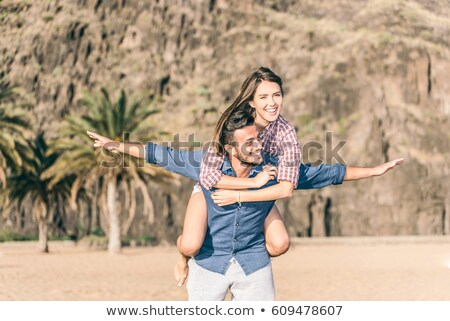 affectionate teenage couple having fun on beach stock photo © monkey_business