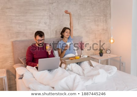 happy yawning young woman in pajama with juice Stock photo © dolgachov