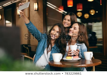 Photo of happy young woman smiling and drinking coffee takeaway Stock photo © deandrobot