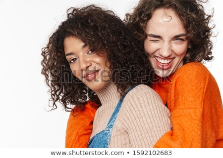 Portrait of cheerful multinational women winking and hugging Stock photo © deandrobot