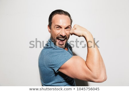 Portrait of a muscular man posing over white background Stock photo © deandrobot