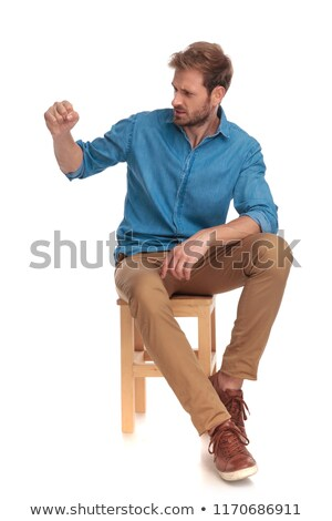 side view of an agry guy sitting on a chair stock photo © feedough