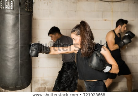 Boxer using punching bag in gym Stock photo © IS2