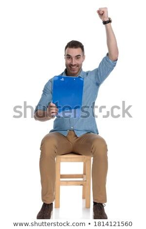 Uśmiechnięty człowiek sukces posiedzenia notatnika Zdjęcia stock © feedough
