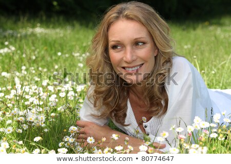 Blond woman laid in field full of daisies Stock photo © photography33