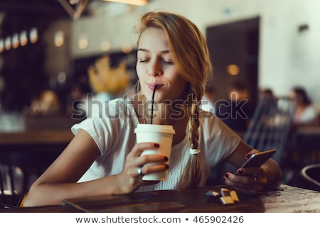young woman drinking coffee and using a smartphone in cafe stock photo © vlad_star