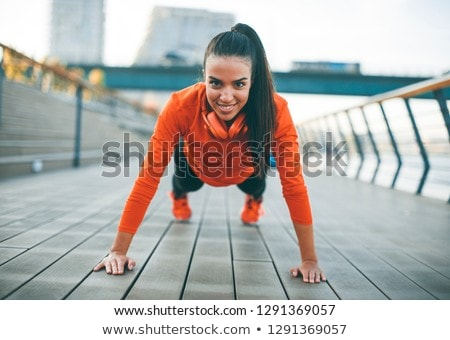 Young woman exercises on the promenade after running Stock photo © boggy