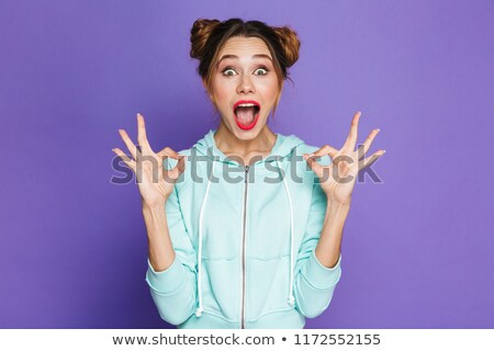 Portrait of excited woman with two buns shouting and showing thu Stock photo © deandrobot