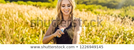 Stock photo: Woman spraying insect repellent on skin outdoor BANNER, LONG FORMAT