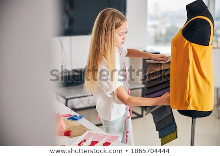 Side view of young Caucasian blonde female fashion designer talking on mobile phone while working at Stock photo © wavebreak_media