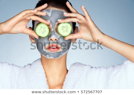 Smiling adult woman with cosmetic cream and cucumber mask Stock photo © dashapetrenko