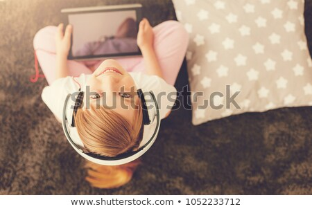 Stock photo: pretty girl listening music and smiling to you