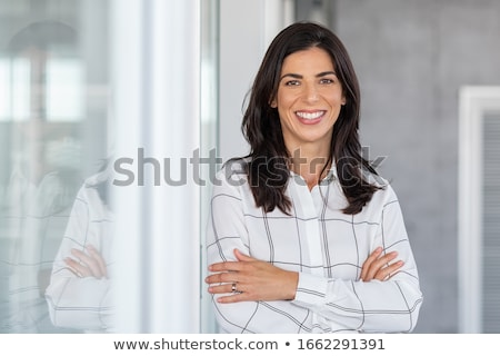 smiling businesswoman at office glass wall stock photo © dolgachov