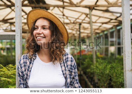Florist woman 20s working in greenhouse over plants Stock photo © deandrobot