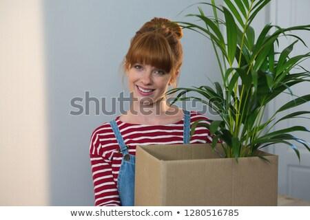 Portrait of female carpenter holding a plant at home Stock photo © wavebreak_media