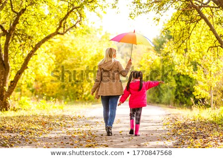 An adult woman walks with her little daughter in an alley in a public Park between the trees Stock photo © ElenaBatkova