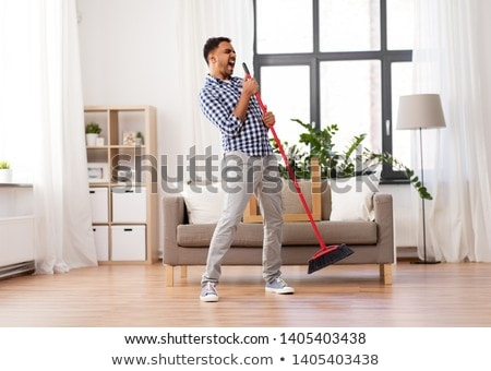 man with broom cleaning and singing at home Stock photo © dolgachov