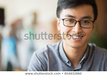 close up image of happy asian male student in eyeglasses stock photo © deandrobot