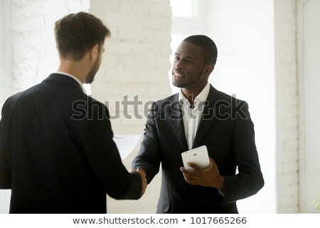 Two young business partners shaking hands after making deal in factory Stock photo © pressmaster
