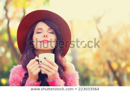 hands with cup of tea, autumn leaves and hat Stock photo © dolgachov