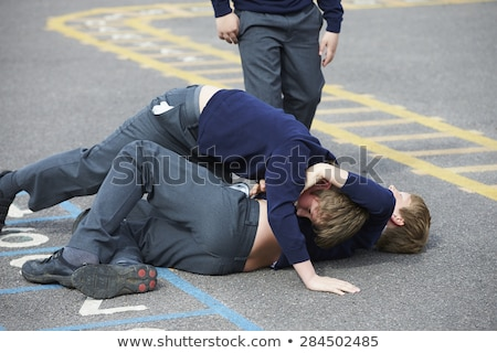 two boys fighting in playground stock photo © lopolo