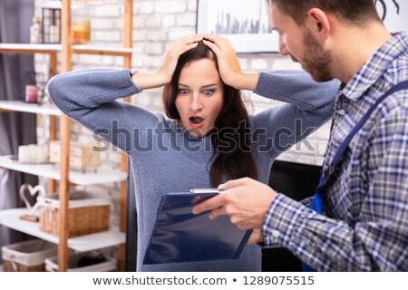 Technician Showing Invoice To Shocked Woman Stock photo © AndreyPopov
