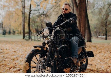 Male motorcyclist drives in nature on fast bike, wears shades, black jacket, gloves, jeans and boots Stock photo © vkstudio