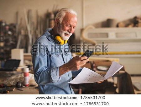 senior craftsman looking at a blueprint Stock photo © photography33
