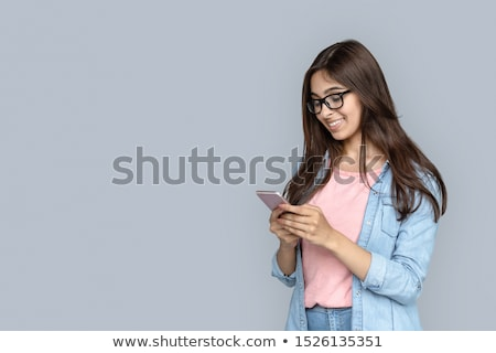 young lady standing and holding a phone with copy space stock photo © ra2studio