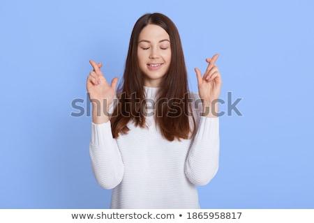 woman having ones fingers crossed against a white background stock photo © wavebreak_media