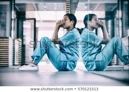 Bezorgd verpleegkundige vergadering vloer ziekenhuis gang Stockfoto © wavebreak_media
