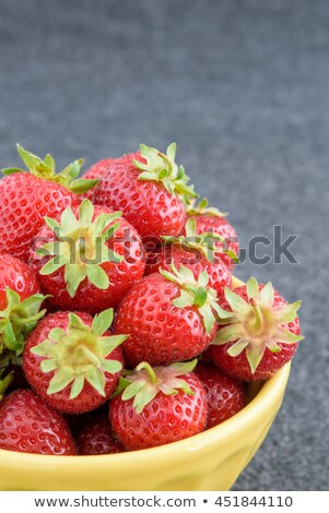 Closeup juicy freshly picked strawberries with green stems in a ceramic plate on a black concrete ba Stock photo © artjazz