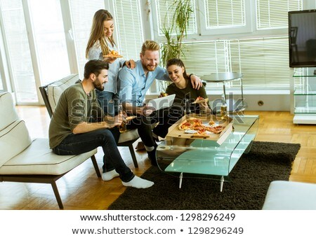 Young people eating pizza, drinking cider and watching digital t Stock photo © boggy