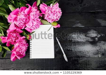 Stock photo: Peony flowers on black background with note or diary a