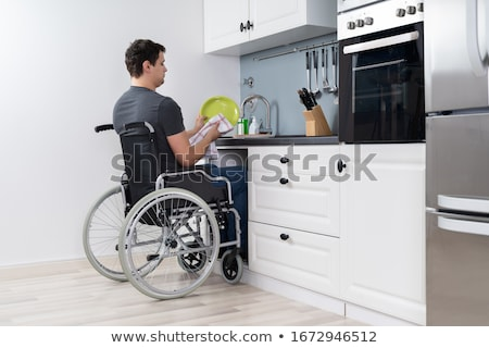 Handicapped Man Cleaning Dishes In Kitchen Stock photo © AndreyPopov