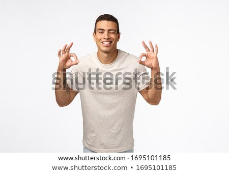 Cheeky carefree and unbothered young hispanic muscline man in t-shirt showing okay, no problem or pe Stock photo © benzoix