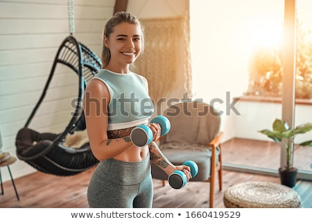 Woman exercising with dumbbell. Stock photo © iofoto