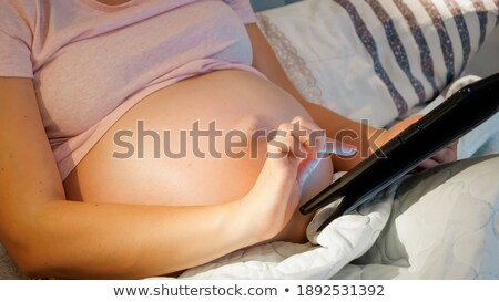 Pregnant woman using tablet in the evening Stock photo © d13
