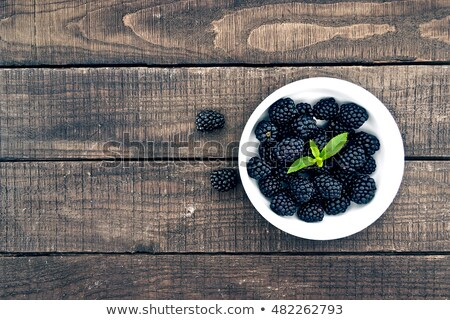 Fresh blackberry with leaves on wooden background close up Stock photo © yelenayemchuk