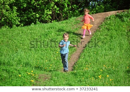 Boy and girl running down a field  Stock photo © IS2