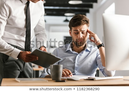 Displeased man sitting in office working with computer near his colleague who showing clipboard with Stock photo © deandrobot