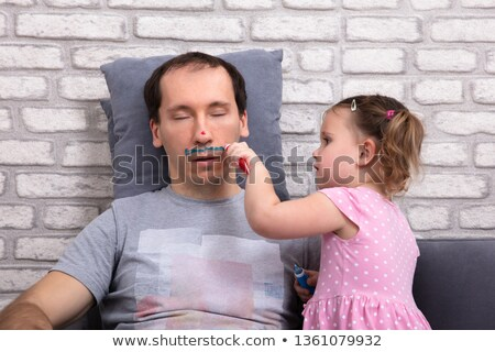 girl painting fathers face with color tube stock photo © andreypopov
