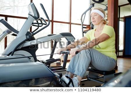 Senior vrouw roeien machine fitness gymnasium Stockfoto © Kzenon