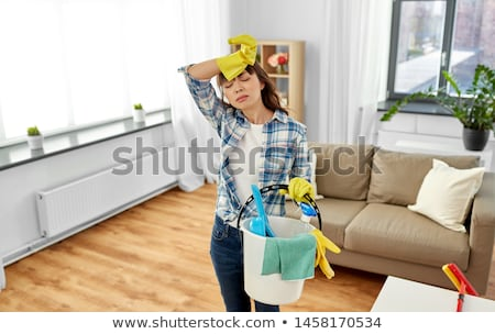 tired woman with bucket and cleaning stuff at home Stock photo © dolgachov