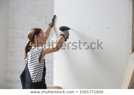 Woman drilling into wall Stock photo © photography33