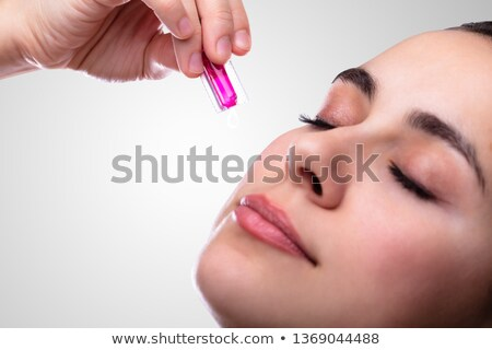 Female Hand Squeezing Vitamin Capsule On Face Stock photo © AndreyPopov